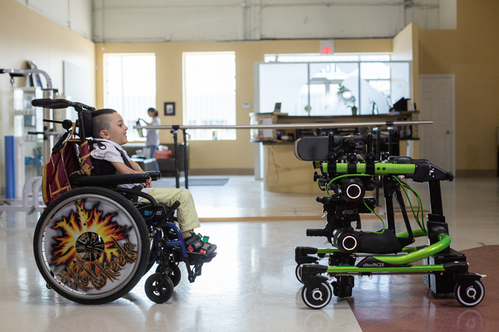 Boy in wheelchair looking at Trexo Plus walking system